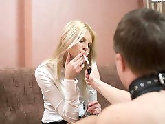 Smoking bitch in high black latex boots humiliates her slave and puts her cig out against his...