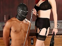 Mz. Berlin trusses her slave's ballsack cock-squeezing and makes him pull against his ball bondage until he can pull no further.  She whips and slaps his culo before having him crawl onto the restrain bondage sofa so she can truss off his ball restrain bondage to the end of the table.  She dishes out a brutal caning while he pulls on his ball bondage.  She trades in the rattan crop for a solid wooden whip.  Then she flicks and pinches his tightly bound balls.