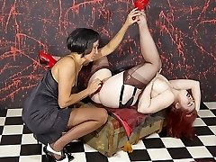 Strapon Jane bends this busty lesbian redhead over and smashes her pussy with a big red strapon