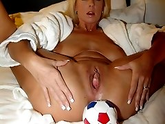 Stuffing some huge balls into her gaping cunt.