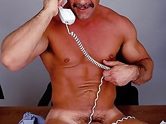 Mature gay bodybuilder Anthony Lopez getting on top of his office desk to stroke his hard...