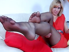 Seductive blondie lowers her smooth pantyhose while showing her delicious feet