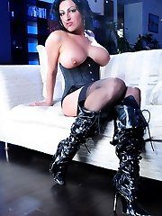 Dark-haired bombshell in classy black stockings and boots rams a red dildo