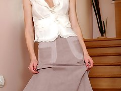 Dazzling blondie hikes up her skirt changing into dark-skinned hose on the stairs