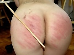 Naked young beauty bent over the desk and caned hard on her upturned buttocks
