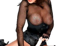 Glamorous bombshell in sexy lingerie and fishnet stockings strapons a dildo to pose on camera