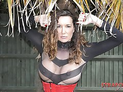 Busty brunette Strapon Jane is outdoors in a red corset and high heels sporting a big black...