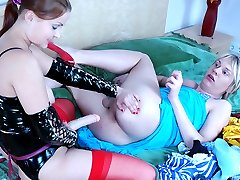 Horny chick in latex lets a sissy guy suck and ride on her huge strap-on