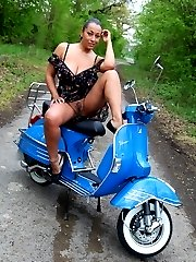 Danica poses outdoors on a scooter