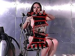 Brunette brunette slave in latex corset takes candles and covers her body with a wax