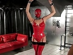 Beautiful female slave in red latex outfit prays for mercy after being unwrapped by her dommes