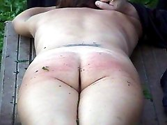 Outdoor convent caning for naked girl tied down and brutally striped on her quivering bare ass