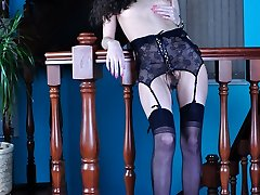Slender leggy brunette in a dark-hued bustier with matching nylons on the stairs