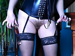 Busty gal toys her hair pie in a leather corset with attached to it nylons
