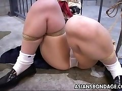 She is roped up to the prison cell and toy fucked