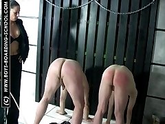 Two naked guys caned on their bare asses by leather clad mistress with great tits