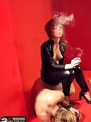 Smoking lady in latex uses her slave as an ashtray