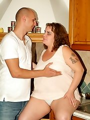 Mindy joins her junior lover in the kitchen to have her fat pussy plugged with a dick