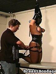 Masked and corseted - a pain slut is introduce to tit bondage.