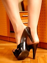 Hot gal admires her high heel sandals and her well-maintained nyloned feet
