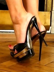 Busty blond beauty's stiletto heels almost pierce through slave's soft skin