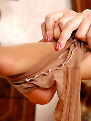 Lovely girl caresses her sexy feet thru stockings before wearing high heels