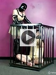 Submissive latex slave is teased in his cage by latex Mistress