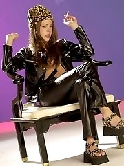 Sexy smoking babe on a chair in black latex outfit