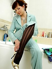 Horny chick strips her trouser suit and wets her patterned hose in the tub