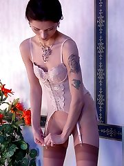Hottie changing her tan stockings to red ones before fondling her beaver