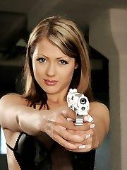 A brunette beauty posing with a gun.