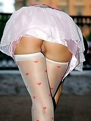 White skirt of gal in stockings hardly covering her upskirt