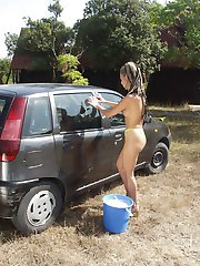 Young blonde taking time to soap her naked body while washing the car outdoors!
