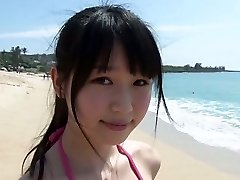 Slim Asian chick Tsukasa Arai walks on a sandy beach under the sun