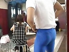 Muscular guy flashes very cute buxomy Japanese chick in a bar