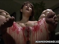 Asian babe get her privates decorated in wax.