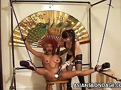 Restrained Asian female tormented by her smoking hot dominatrix