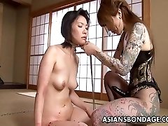 Tattooed up Asian domme strap on penetrating the sub
