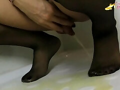 Blonde tgirl in black stockings urinating on her own feet
