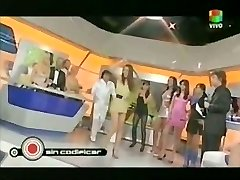 Sexy singer in a TV display lets the audience witness up her miniskirt