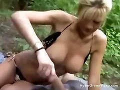 Big tit cougar in bathing suit jerks off her boyfriend in the woods