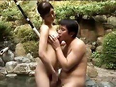 Breasty slut romping an Asian man in a pool