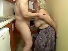 Super-naughty, blond granny is playing with her tits and her lovers dick, in the kitchen