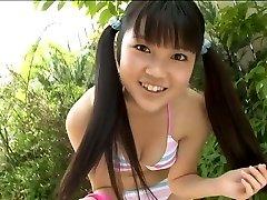 Slatka korejski student pozira u bikiniju u vrtu