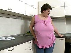 Gross brunette mummy pulls up her leg to jerk with finger