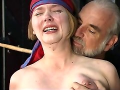 Cute young blonde with perky tits is held for nipple clamp play