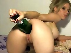 Kinky blonde uses the fat end of a bottle to stick in her culo