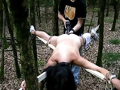 Bound to a cross and fucked with a huge dildo in the forest