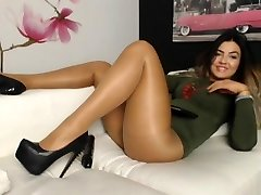 Youthfull girl in shining tan pantyhose on couch 2