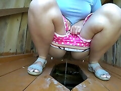 Girl with a highly fur covered pussy, peeing in a street public toilet